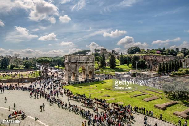 tourists at triumphal arch, rome, italy - image foto e immagini stock