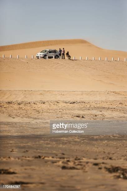 Tourists at vehicle in namibian desert