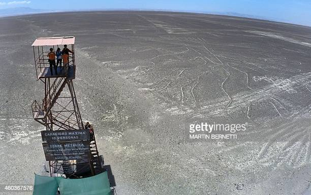 Tourists atop a mirador look at the Nazca Lines in Nazca Peru some 435 kms south of Lima on December 12 2014 Geoglyphs can be seen only from atop the...