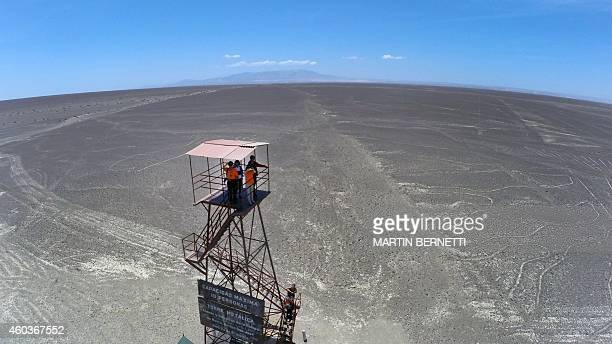 Tourists atop a mirador looks at the Nazca Lines in Nazca Peru some 435 kms south of Lima on December 12 2014 Geoglyphs can be seen only from atop...