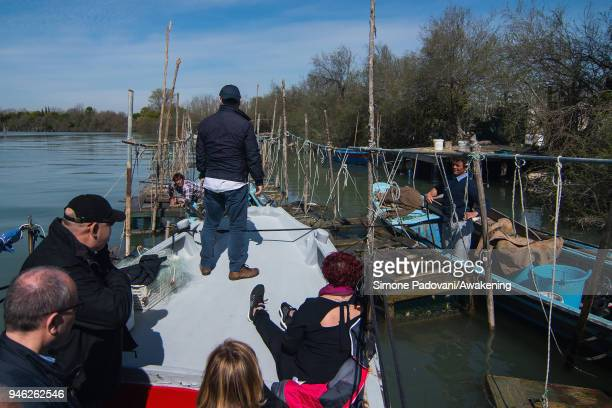 Tourists attend a fishing tour of 'Moeche' organized by Cooperativa San Marco in Burano on April 14 2018 in Venice Italy At the beginning of the...