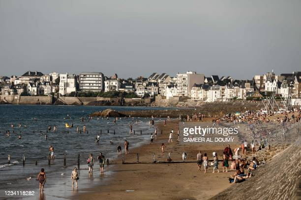 Tourists bathe on a beach by the sea in Saint-Malo, western France, on July 22, 2021.