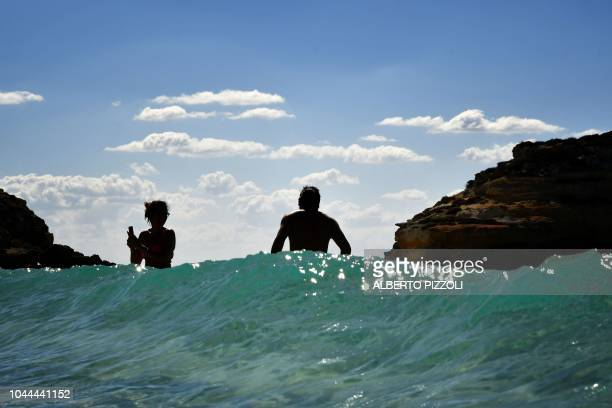 Tourists bathe on the beach of the Isola dei Conigli in Lampedusa on September 27 2018 Five years after the worst shipwreck of its history the...