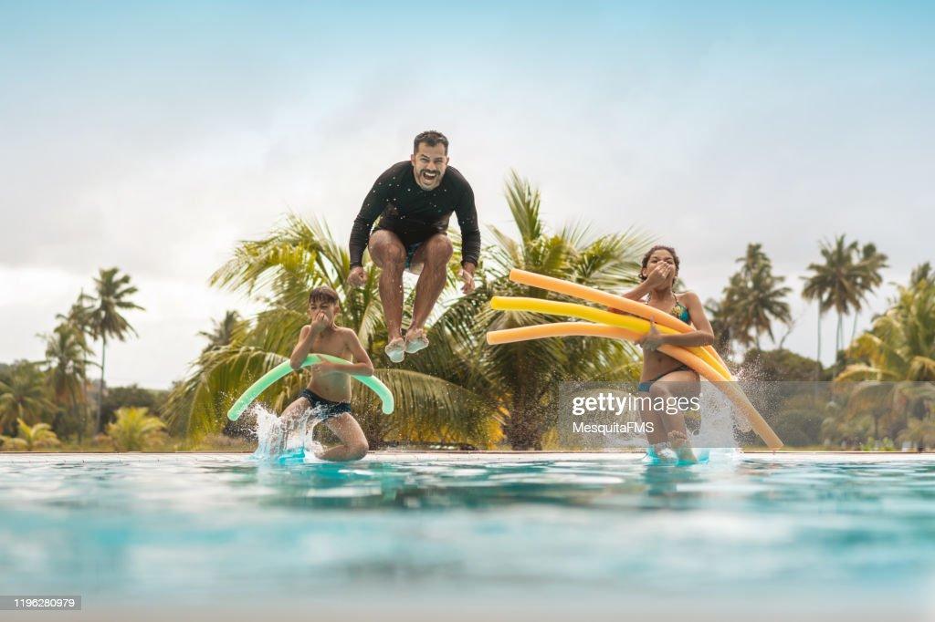 Tourists bathing in resort swimming pool : Stock Photo