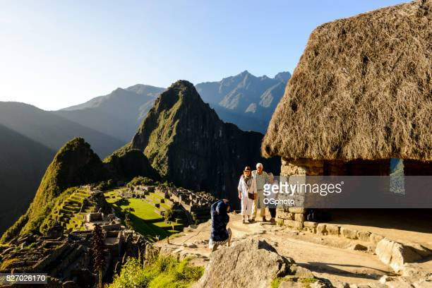 Tourists being photographed overlooking Machu Picchu.