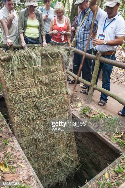 Tourists beside a booby trap at Ben Dinh Cu Chi near Ho Chi Minh City Vietnam