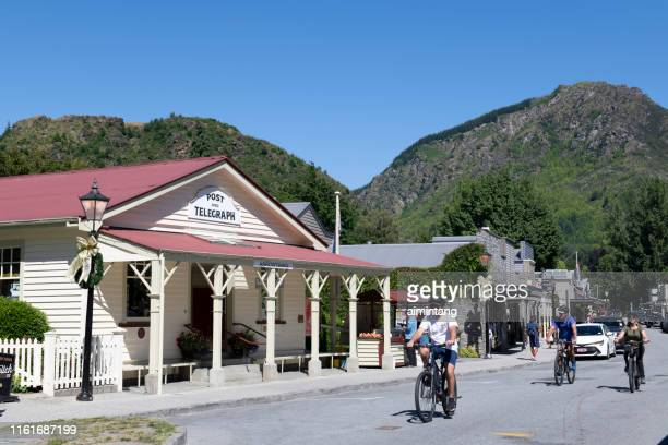 tourists biking on street of arrowtown - arrowtown stock pictures, royalty-free photos & images