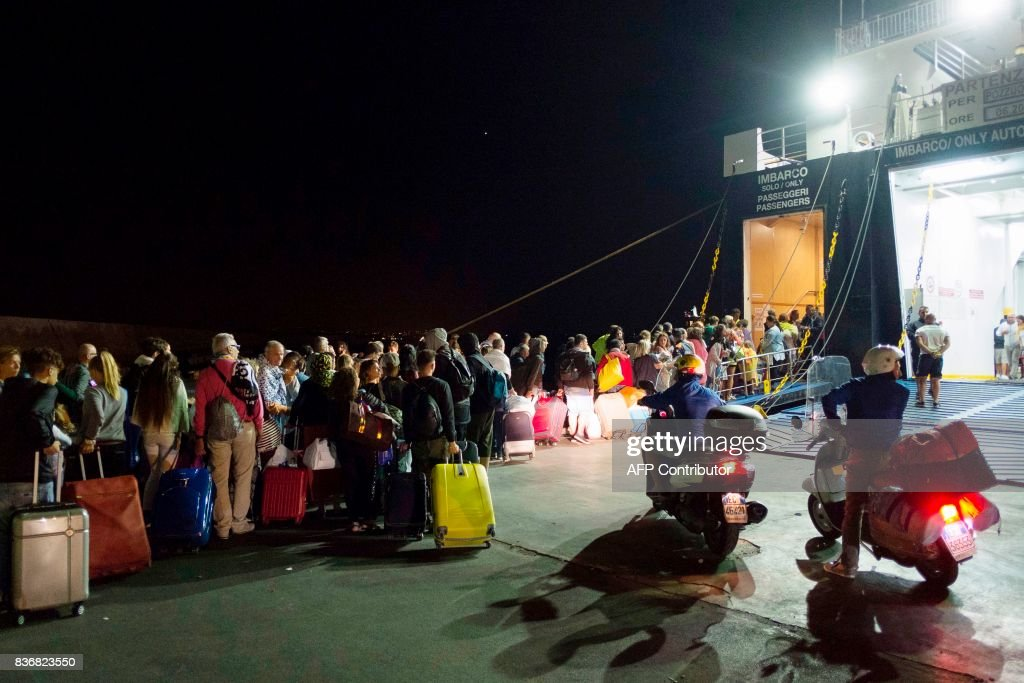 TOPSHOT - Tourists board a ferry early morning in Ischia, on August 22, 2017, after an earthquake hit the popular Italian tourist island off the coast of Naples, causing several buildings to collapse overnight. A magnitude-4.0 earthquake struck the Italian holiday island of Ischia, causing destruction that left two people dead at peak tourist season, authorities said, as rescue workers struggled early to free two children from the rubble. / AFP PHOTO / Eliano IMPERATO