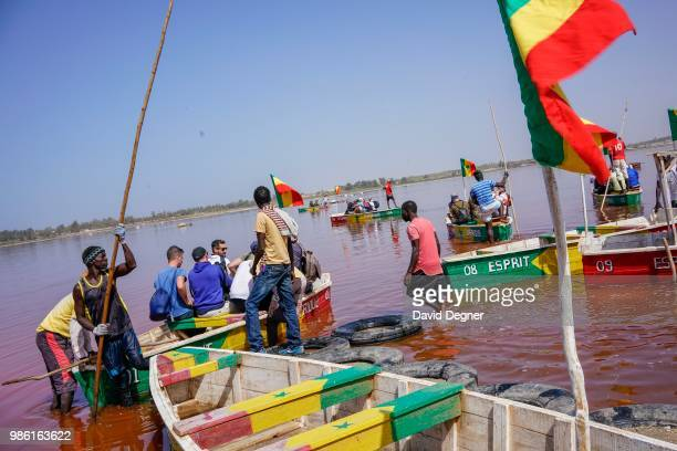 Tourists board boats to travel across Lac Rose on the edge of Dakar Senegal Lac Rose is a saline lake that gets its color from a special type of...