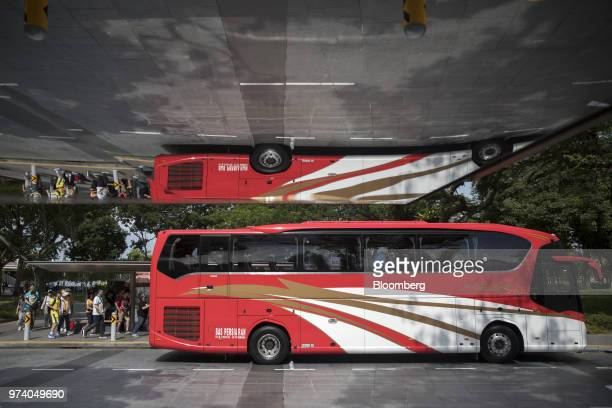 Tourists boarding a bus are reflected in a bus shelter in Singapore on Wednesday June 13 2018 Tourism as well as the consumer sector will likely see...
