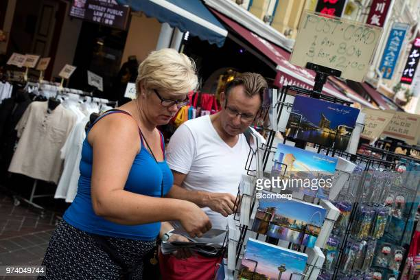 Tourists browse postcards at a stall in the Chinatown area of Singapore on Wednesday June 13 2018 Tourism as well as the consumer sector will likely...