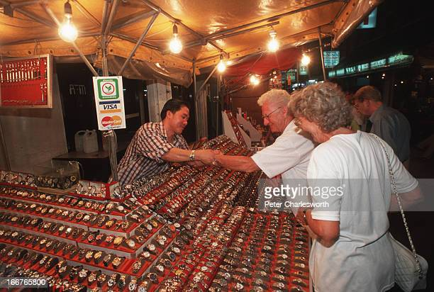 Tourists buy fake pirated watches from a market stall on the beach road in Patong one of the main tourist streets in a popular area of this resort...