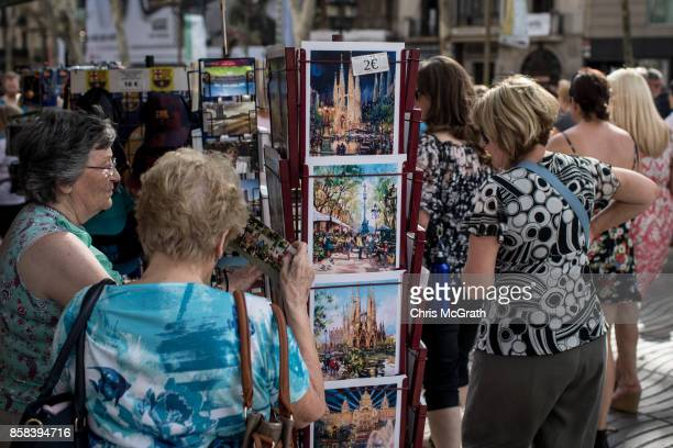 Tourists buy postcards on Barcelona's famous La Rambla street on October 6 2017 in Barcelona Spain Tension between the central government and the...