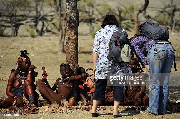 Tourists buy souvenirs from Himba women on August 19 2010 in the village of Ohungumure 15 kms west of Opuwo in northern Namibia AFP PHOTO / STEPHANE...