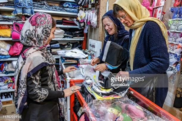 tourists buying clothes in an iranian store - isfahan province stock pictures, royalty-free photos & images