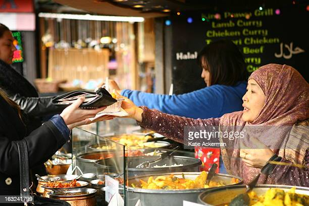 Tourists buying food from a Asian food stall in Camden Market, London