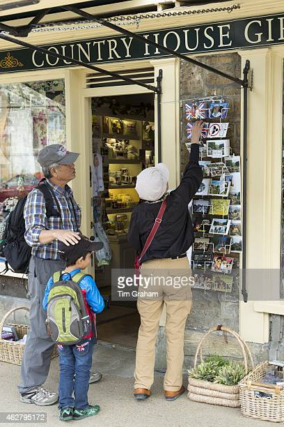 Tourists buying postcards from souvenirs and gifts shop in Burford in The Cotswolds Oxfordshire UK