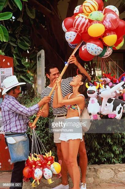 tourists buying toy balloons, cabo san lucas, mexico - halbinsel niederkalifornien stock-fotos und bilder