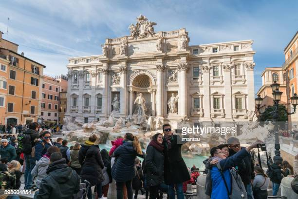 tourists by the trevi fountain in rome, italy - trevi fountain stock photos and pictures