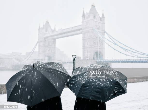 tourists by tower bridge in snow - horizon over land stock pictures, royalty-free photos & images