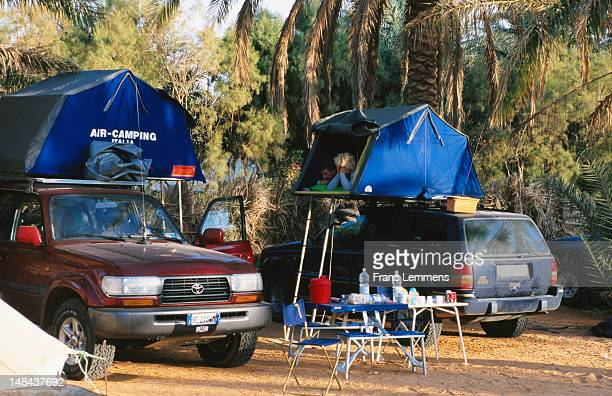 Tourists camping atop four wheel drives at oasis in Sahara Desert..
