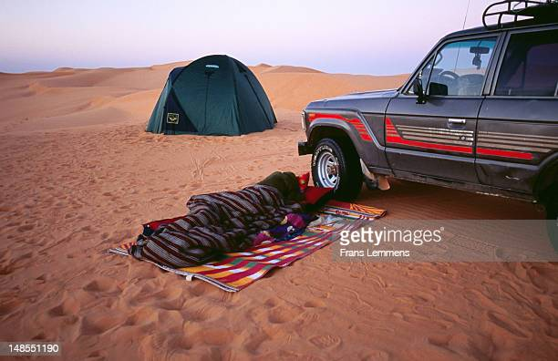 Tourists camping on the sand by a four wheel drive, Sahara Desert.