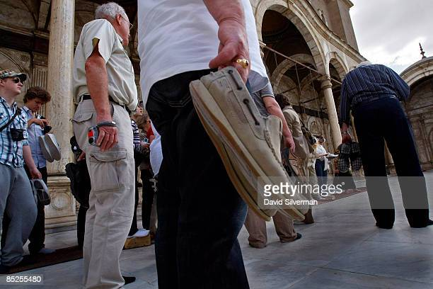 Tourists carry their shoes as they visit the 19th century Ottomanera Muhammad 'Ali mosque an alabaster covered landmark which dominates the Citadel...