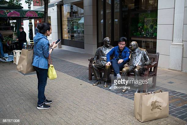 Tourists carrying Burberry Group Plc luxury goods branded shopping bags take photographs with sculptures of former British Prime Minister Winston...