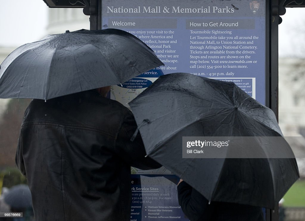Tourists check a map of the National Mall on the west side of the Capitol as they shield themselves form the rain with umbrellas on Monday, Nov. 30, 2009.