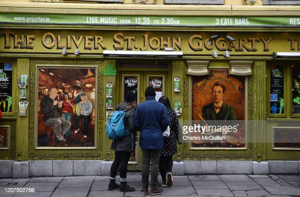 Tourists check to see if a bar in the Temple Bar district is open following the cancellation of the annual Saint Patricks Day parade and celebrations...