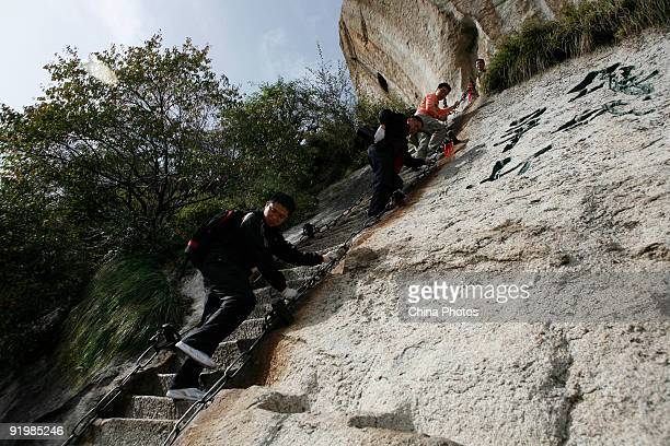 Tourists climb down a steep path on the Huashan Mountain on October 18 2009 in Huayin Shaanxi Province China Huashan located at an altitude of 21549...