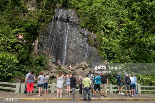 Tourists climb rocks on the La Mina Waterfall in El Yunque Rain Forest on September 19 2018 in Rio Grande Puerto Rico Parts of the popular...
