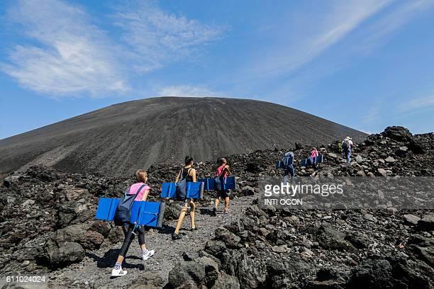 Tourists climb the Cerro Negro volcano to enjoy sandboarding in Leon some 100km northwest from Managua on September 24 2016 / AFP / INTI OCON