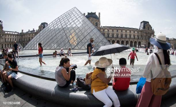 Tourists cool themselves at the fountain in front of the Louvre Pyramid in Paris on August 7 during an ongoing heatwave in Europe
