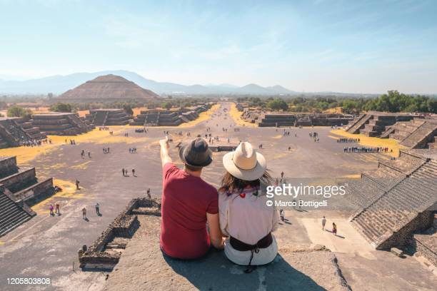 tourists couple admiring the view of teotihuacan archaeological site, mexico - mexico stock pictures, royalty-free photos & images