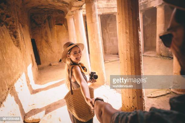 tourists couple holding hands in ancient archaeological site in greece - old ruin stock pictures, royalty-free photos & images
