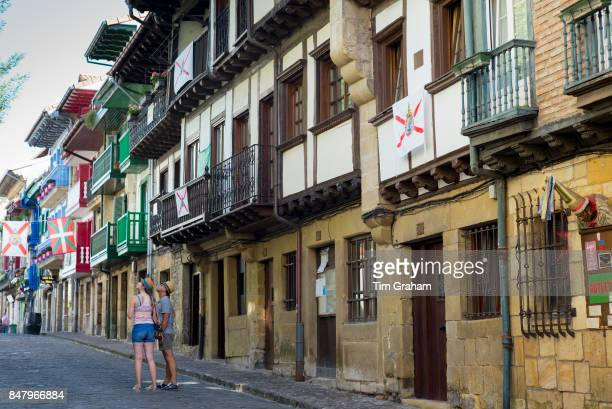 Tourists couple in street scene in alleyway of old town Hondarribia in Basque Country Spain