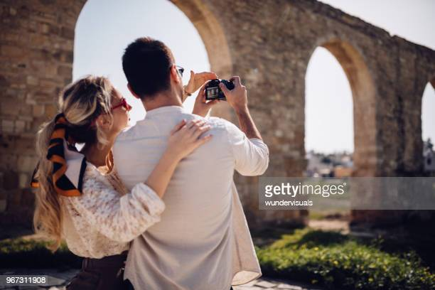 Tourists couple with camera taking photos of ancient stone monument
