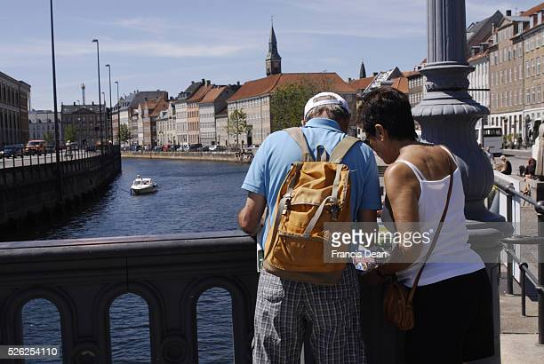 Tourists couple studing city map whgile standing at Hojbro bridge canal 28 June 2011