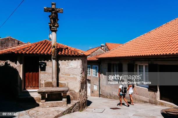 COMBARRO PONTEVEDRA GALICIA SPAIN Tourists couple walking among stone houses and cruceiros in the old town