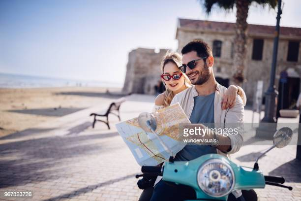 tourists couple with retro scooter reading map on mediterranean island - turista foto e immagini stock