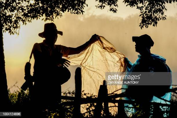 Tourists cover themselves with a raincoat on June 29 2018 in the rainforest overlooking the waterfalls at Vitoria Falls After nearly two decades in...