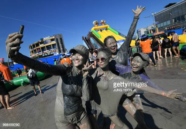 Tourists covered with mud pose for a selfie during the 21th Boryeong Mud Festival at Daecheon beach in Boryeong on July 14 2018 The annual festival...