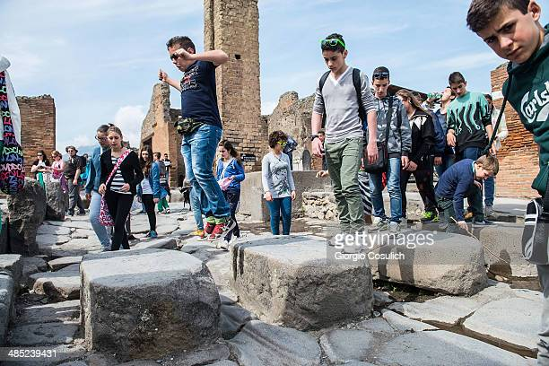 Tourists cross a street at the archeological site on April 12 2014 in Pompei Italy The Italian government has enacted a series of provisions for the...