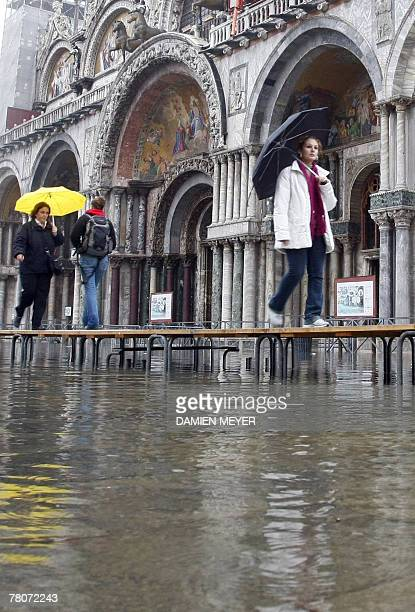Tourists cross San Marco's place flooded with water 23 November 2007 in the Italian historic city of Venice known for its canals and gondolas The...