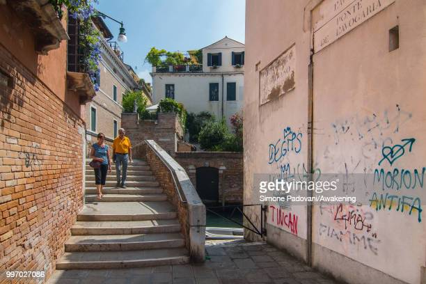 Tourists cross the bridge of Avogaria to walk in Calle de l'Avogaria where there are graffiti and tags on the walls on the way to reach San...