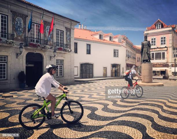 tourists cycling near cascais city hall, portugal - cascais stock photos and pictures