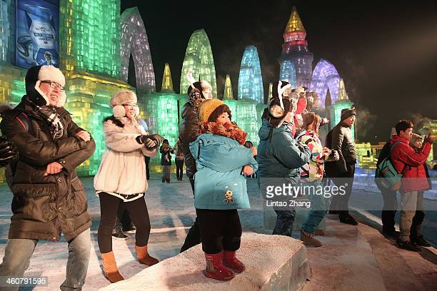 Tourists dance at the Grand Ice and Snow World during the 30th Harbin International Ice Snow Sculpture Festival on January 5 2014 in Harbin China...