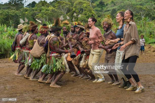tourists dancing with traditional papuan dancers - tari stock pictures, royalty-free photos & images
