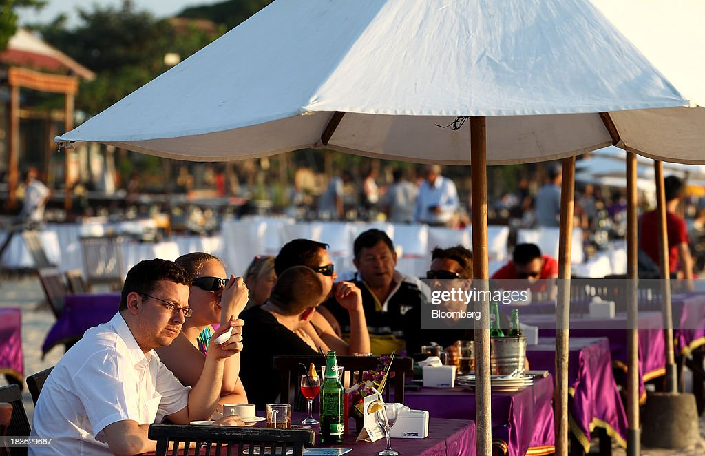 Tourists dine at a beachside restaurant in Jimbaran, Bali, Indonesia, on Saturday, Oct. 5, 2013. Indonesia's central bank kept its key interest rate unchanged after its most aggressive tightening cycle in almost eight years as inflation pressure eased. Photographer: SeongJoon Cho/Bloomberg via Getty Images